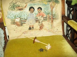handspun single boll of brown cotton and 21 skeins. Background, grandma Arelia's embroidered  wall hanging.
