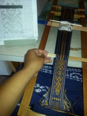 Weaving the original floral design.
