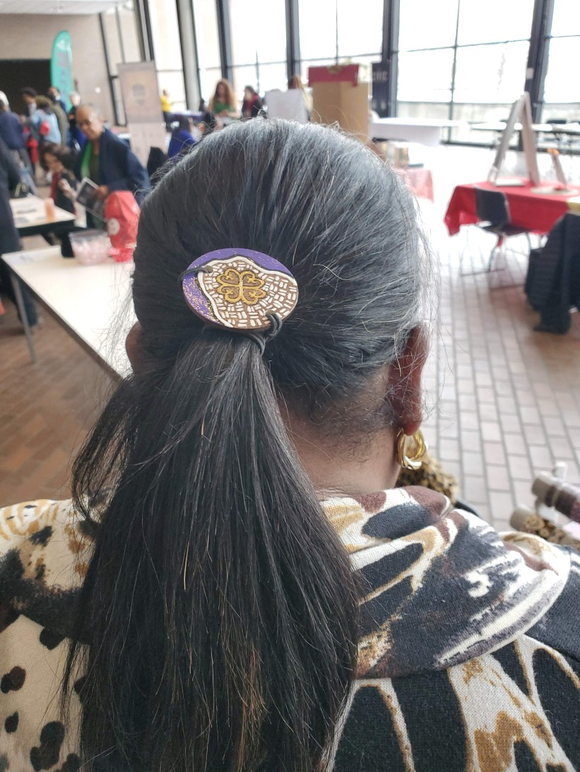Sanita wearing her new Adinkra symbol hairtie which means God's alter and symbolizes His protection over all creation